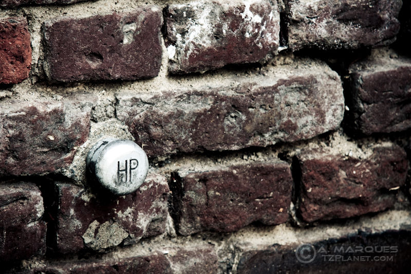"""A small fixture on a brick wall, marked """"HP""""."""